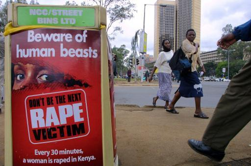 People walk past a poster bearing a message against rape on a street of Nairobi, Kenya