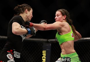 Miesha Tate (R) punches Sara McMann in their bantamweight bout during UFC 183 in January. (Getty)