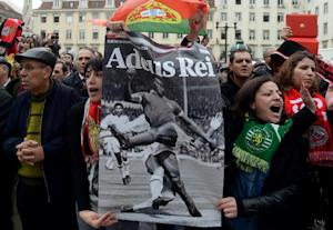 Two women hold a placard depicting Benfica football …