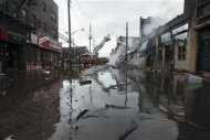Firefighters work to extinguish a fire on a flooded street in the Rockaways section of New York, October 30, 2012. REUTERS/Keith Bedford