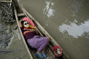 A resident rests in a boat floating in floodwaters…