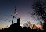 A U.S. flag flys at half-staff as vehicles drive on Main Street in downtown Newtown, Conn., as the sun rises the morning after a gunman opened fire inside a nearby elementary school, Saturday, Dec. 15, 2012. The man allegedly killed his mother at their home and then opened fire Friday inside the Sandy Hook Elementary school, massacring 26 people, including 20 children. (AP Photo/Julio Cortez)