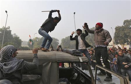 A demonstrator breaks the windshield of a police vehicle as others shout slogans in front of the India Gate during a protest in New Delhi