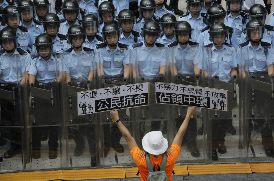 """A protester raises placards that read """"Occupy Central and Citizen Against Order""""  in front of riot policemen outside the government..."""
