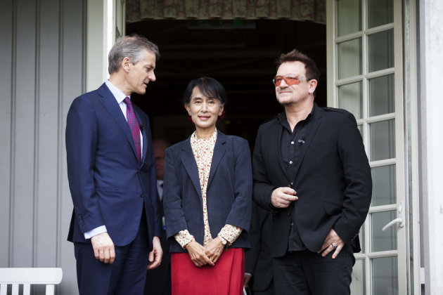 From left, Norwegian Foreign Minister Jonas Gahr Stoere, Myanmar opposition leader Aung San Suu Kyi and Irish singer and activist Bono pose for the media after they attending a conference of the Oslo
