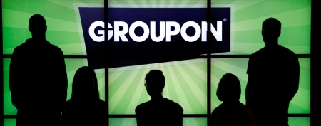 Groupon employees pose with the company logo in the lobby of the online coupon company's Chicago office. (AP Photo/Charles Rex Arbogast)