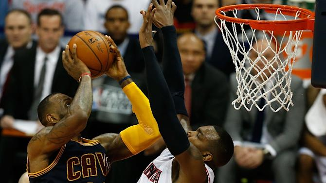 LeBron James (left) of the Cleveland Cavaliers shoots over Paul Millsap of the Atlanta Hawks during game one of the Eastern Conference finals at Philips Arena on May 20, 2015 in Atlanta, Georgia