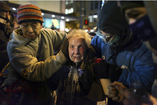 Seattle activist Dorli Rainey, 84, reacts after being hit with pepper spray during an Occupy Seattle protest on Tuesday, Nov. 15, 2011 at Westlake Park in Seattle. Protesters gathered in the intersection of 5th Avenue and Pine Street after marching from their camp at Seattle Central Community College in support of Occupy Wall Street. Many refused to move from the intersection after being ordered by police. Police then began spraying pepper spray into the gathered crowd hitting dozens of people. (AP Photo/seattlepi.com, Joshua Trujillo)  MAGS OUT; NO SALES; SEATTLE TIMES OUT; TV OUT; MANDATORY CREDIT