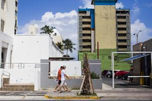 Two men walk past a vacant building on November 12,…