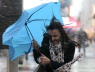 A woman struggles with her umbrella in the wind and snow in New York, November 7, 2012. A wintry storm dropped snow on the Northeast and threatened to bring dangerous winds and flooding to a region still climbing out from the devastation of superstorm Sandy.  REUTERS/Brendan McDermid (UNITED STATES - Tags: DISASTER ENVIRONMENT)