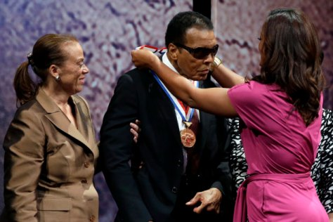 Retired boxing champion Muhammad Ali, center, receives the Liberty Medal from his daughter Laila Ali with his wife Lonnie Ali at his left during a ceremony at the National Constitution Center, Thursday, Sept. 13, 2012, in Philadelphia. The honor is given annually to an individual who displays courage and conviction while striving to secure liberty for people worldwide. (AP Photo/Matt Rourke)