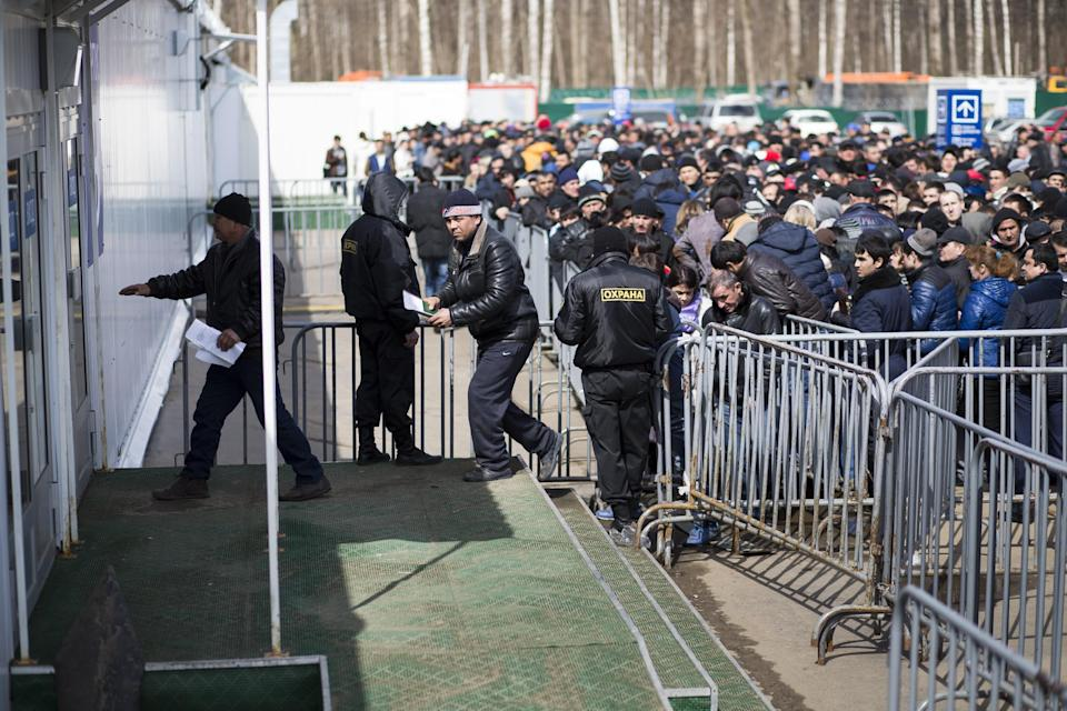 In this photo taken on Wednesday, April  22, 2015, Migrants enter a tent as others stand in line to register at Moscow's migration center in...