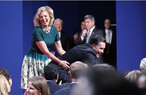Ann Romney holds onto her husband, Republican Presidential nominee Mitt Romney, as he reaches down to shake hands with members of the audience at the conclusion of the final presidential debate in Boca Raton