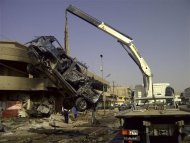 A burnt vehicle is removed from the site of a bomb attack, which killed Shi'ite pilgrims who were making their way to a religious festival, in Baghdad June 13, 2012. Bombs targeting Shi'ite pilgrims in Baghdad and police in southern Iraq killed at least 44 people on Wednesday in a wave of attacks during a major religious festival, police and hospital sources said. The festival was held to mark the anniversary of the death of Shi'ite imam Moussa al-Kadhim, a great-grandson of Prophet Mohammad. REUTERS/Saad Shalash