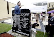 David Silverman, president of American Atheists, stands on a Ten Commandments and says why he thinks it shouldn't be there after Eric Hovind (not pictured), with Creation Today, stood on the new Atheist bench and preached his beliefs during the unveiling of an Atheist monument outside the Bradford County Courthouse on Saturday, June 29, 2013 in Stark, Fla. The New Jersey-based group American Atheists unveiled the 1,500-bound granite bench Saturday as a counter to the religious monument in what's called a free speech zone. Group leaders say they believe it's the first such atheist monument on government property. About 200 people attended the event.(AP Photo/The Gainesville Sun, Matt Stamey)