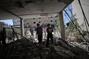 Palestinians inspect the rubble of a destroyed house…