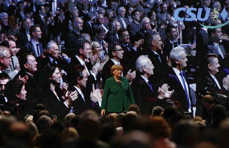 German Chancellor Angela Merkel (C) acknowledges an applause by delegates before her guest speech at a Christian Social Union (CSU) party meeting in Munich October 19, 2012. REUTERS/Michael Dalder