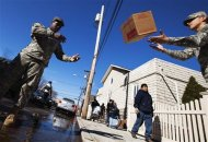 Soldiers from the National Guard help to unload supplies to set up a donation distribution center for victims of superstorm Sandy at St. Camillus School in the Rockaways area of the Queens borough of New York, November 4, 2012. REUTERS/Lucas Jackson
