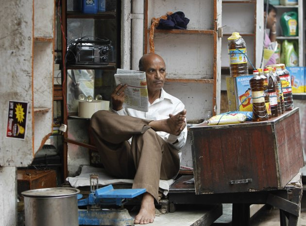 A shopkeeper selling cooking oil reads a newspaper inside his shop at a market in the old quarters of Delhi