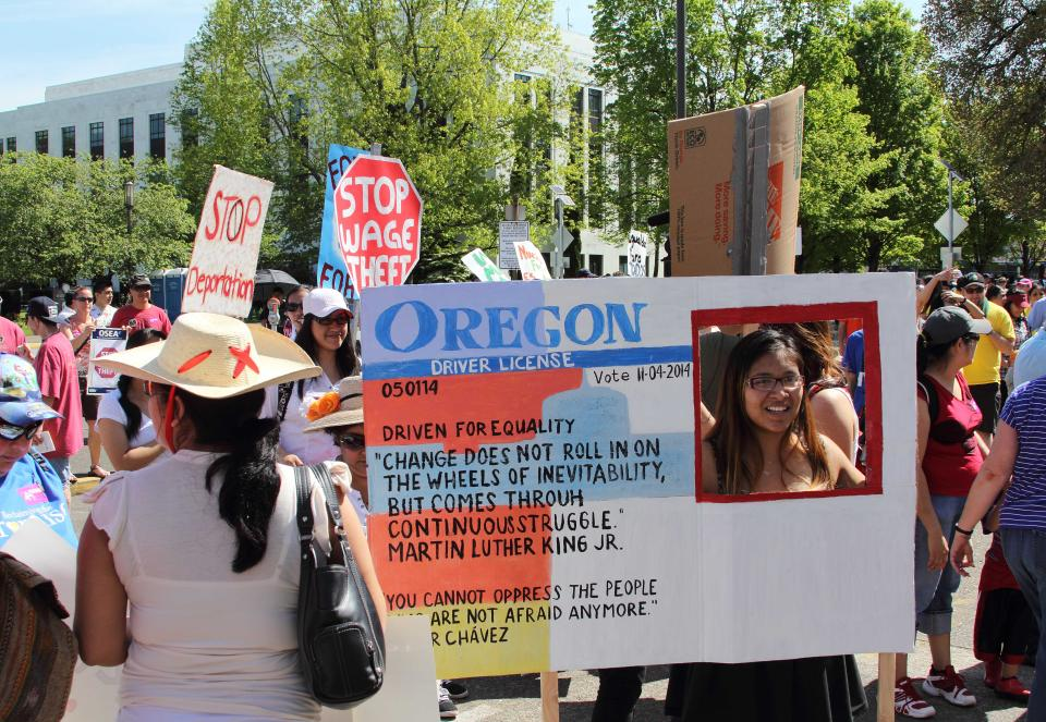FILE - In this May 1, 2014 file photo, Nathalie Marquez holds a sign modeled after an Oregon drivers license at the Capitol, in Salem, Ore.    As...