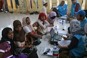 UNHCR workers question ethnic Rohingya women at a temporary …
