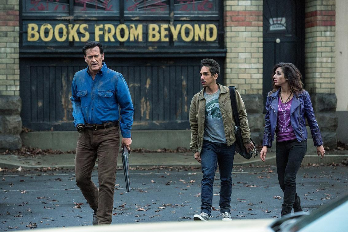 "In this May 22, 2015, publicity image, actor and producer Bruce Campbell, playing the role of Ash Williams, left, walks with actors Ray Santiago, center, playing the role of Pablo Simon Bolivar, and Dana DeLorenzo, playing the role of Kelly Maxwell, during a scene from ""Ash vs Evil Dead"" filmed in Auckland, New Zealand. More than 30 years after the low-budget horror movie ""The Evil Dead"" was released and became a cult classic, Ash is back and premiering on Halloween on cable network Starz. (Matt Klitscher/Starz via AP)"