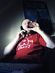 Guy drinking wine and talking on phone, in front of computer