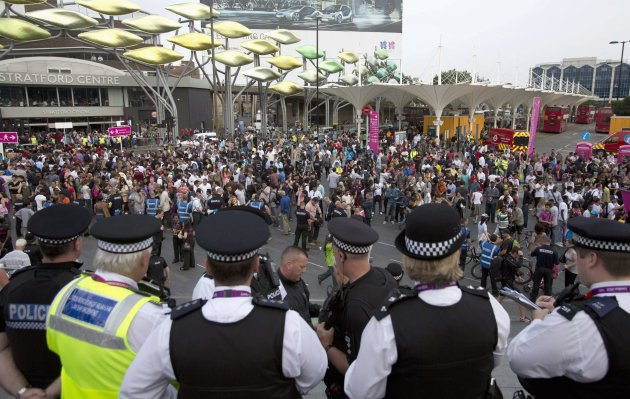 Police officers look on as people at Stratford Station queue to get into the Olympic Park for the opening ceremony of the 2012 Olympic Games in London