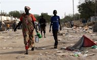 REFILE - CLARIFYING CAPTION People walk past burnt-out shops in Malakal town, 497km (308 miles) northeast of capital Juba, as rebels fighters flee from government attack, December 30, 2013 after South Sudanese soldiers retook the town from rebel fighters. REUTERS/James Akena