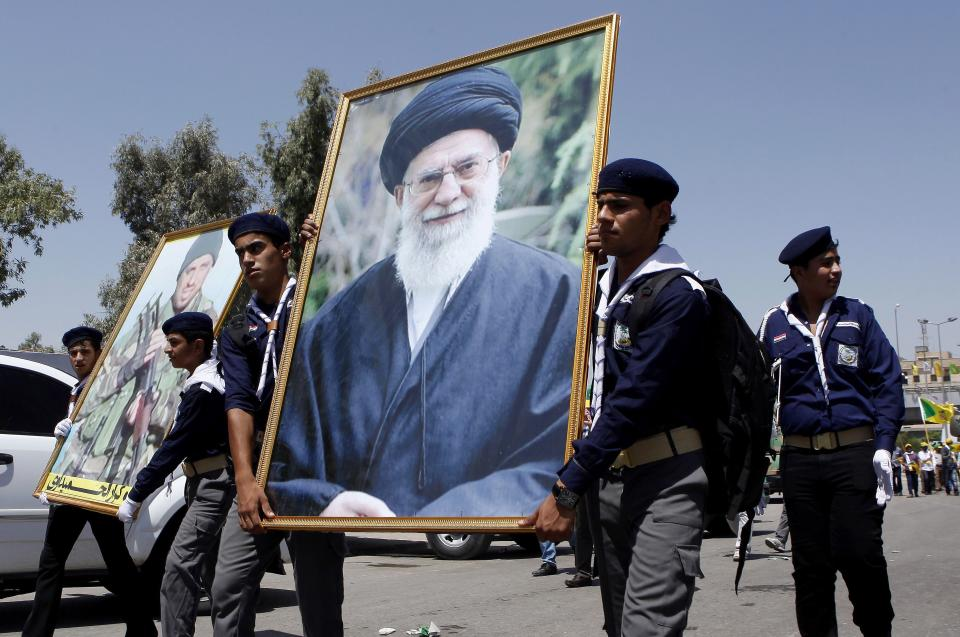 FILE - In this file photo taken on Friday, Aug. 2, 2013, Iraqi Hezbollah scouts parade with a portrait of  Iran's supreme leader Ayatollah Ali...