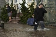 A man walks through floodwaters in the Rockaways section of New York, October 30, 2012. REUTERS/Keith Bedford