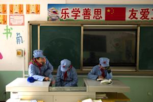 Children dressed in uniforms gather in their classroom …