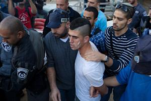 Israeli security forces arrest a Palestinian man (2-R) …