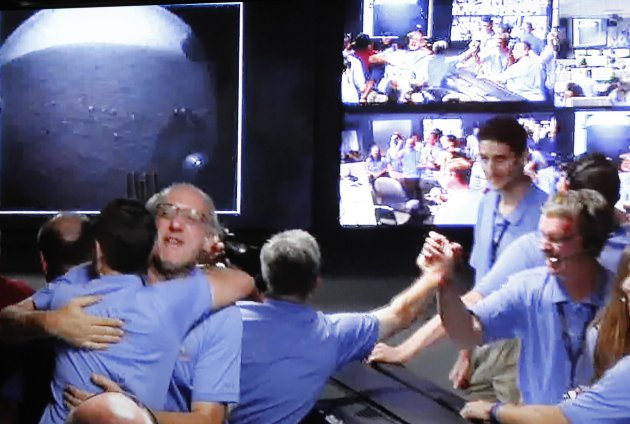 In this image shot off a video screen from NASA TV, members of the Mars Science Laboratory (MSL) team celebrate as the first images are shown on screen from the Curiosity rover