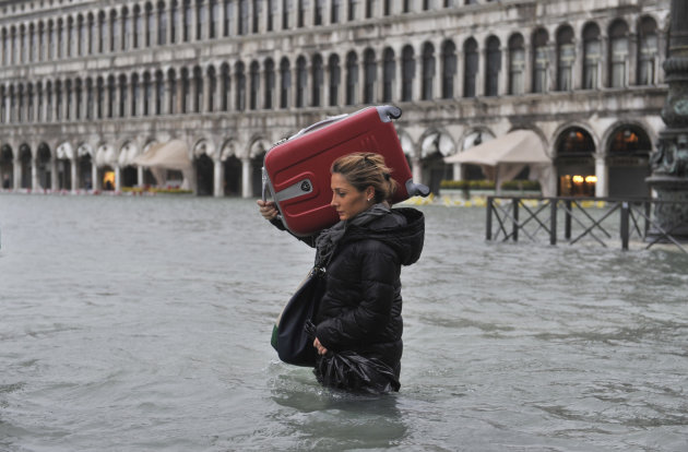 A tourist crosses flooded St. Mark's Square in Venice, Italy, Sunday, Nov. 11, 2012. High tides have flooded Venice, leading Venetians and tourists to don high boots and use wooden walkways to cross S