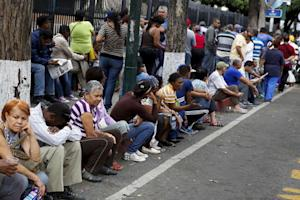 People queue to buy staple items outside state-run…