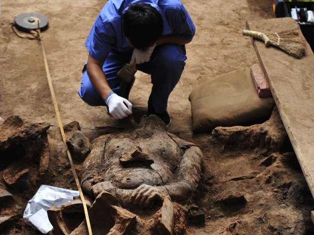 A member of an archaeology team unearths a terracotta warrior at the excavation site inside the No.1 pit of the Museum of Qin Terracotta Warriors and Horses, on the outskirts of Xi'an, Shaanxi province, June 9, 2012. It is the first time that shields have been unearthed during an excavation. A large number of the terracotta warriors and horses bear traces of burn marks, which are suspected to have been caused by Xiang Yu, a military leader who rebelled against the Qin Dynasty (221 BC - 207 BC), according to local media. REUTERS/Stringer (CHINA - Tags: SOCIETY) CHINA OUT. NO COMMERCIAL OR EDITORIAL SALES IN CHINA