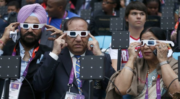 Acting Indian Olympic Association President Malhotra, his wife Krisha and guest Singh of India try on their glasses before the opening ceremony of the London 2012 Olympic Games