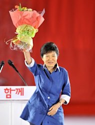 """Park Geun-Hye (centre), the daughter of assassinated dictator Park Chung-Hee, after she was elected as a presidential candidate in a primary held by the New Frontier Party in Goyang, north of Seoul, on August 20. Beaming broadly, Park accepted a bouquet of flowers from party leaders and promised to secure the presidency and create a country """"full of dreams and hope"""". (AFP Photo/Jung Yeon-Je)"""
