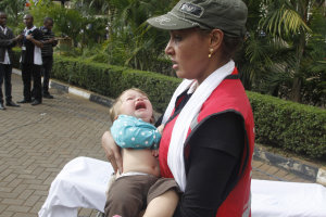 A Red Cross assistant helps a child outside the Westgate …
