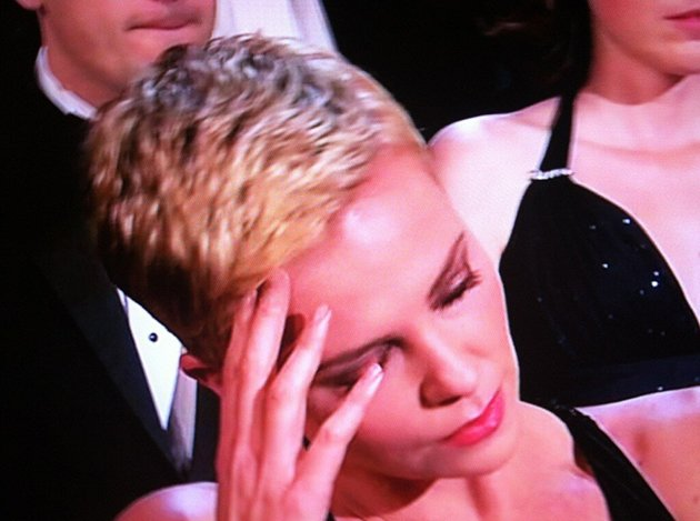 Charlize jokingly bowing her head during the song