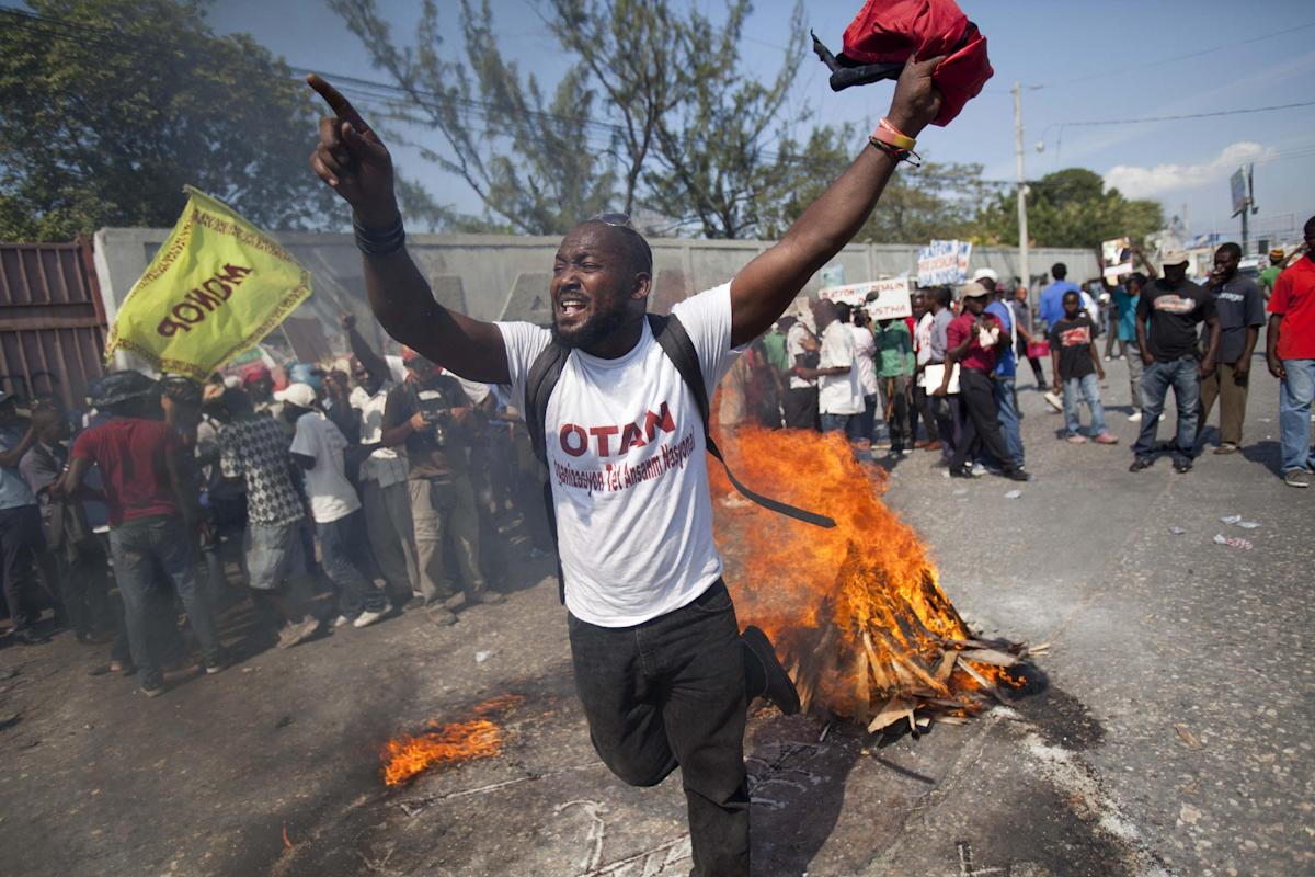 In this Friday, Jan. 23, 2015 photo, a demonstrator uses wood, gas, fire and salt to call forth a spirit to ask for protection, in a voodoo ceremony before the start of a protest demanding the resignation of President Michel Martelly in Port-au-Prince, Haiti. The hardline opposition to Martelly has promised a wave of intensified street protests to try and pressure him from office. Martelly took office in 2011 and is due to leave next year. (AP Photo/Dieu Nalio Chery)