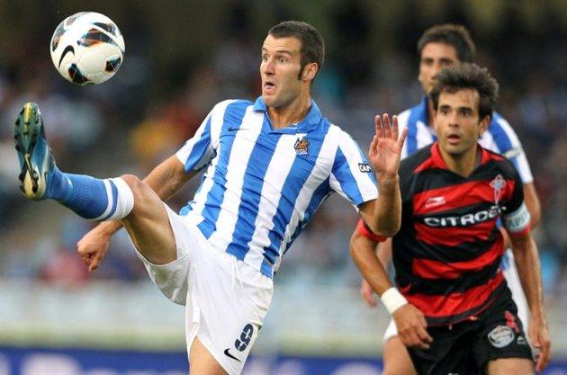 DEP109. SAN SEBASTIÁN, 25/08/2012.- El delantero de la Real Sociedad, Imanol Agirretxe (i), intenta controlar la pelota ante la presión del centrocampista del Celta, Borja Oubiña (d), durante el parti