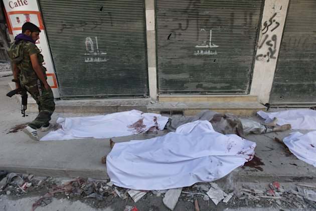 A Free Syrian Army soldier, left, looks at dead bodies laying on a roadside in front of al-Shifa hospital, at al-Shaar neighborhood, in Aleppo city, Syria, Monday Sept. 24, 2012. Syrian warplanes bombed two buildings on Monday in the northern city of Aleppo, killing at least five people including three children from the same family, activists said. (AP Photo/Hussein Malla)