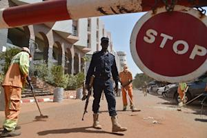 A Malian police officer stands guard as municipal workers …
