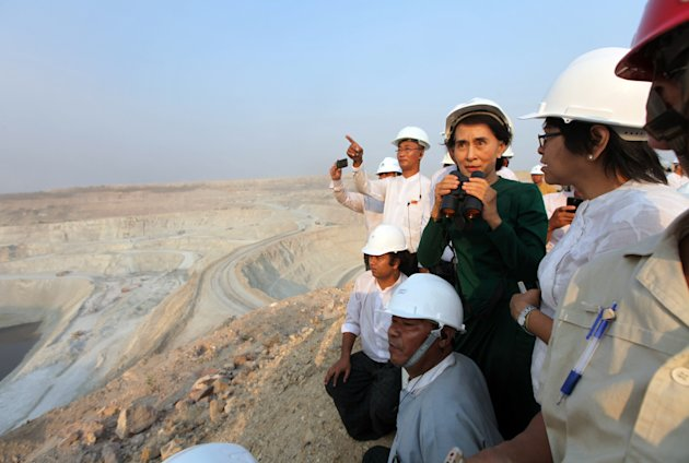 Myanmar's opposition leader Aung San Suu Kyi uses binoculars to look at the Letpadaung copper mine project during a visit to Myanmar Yang Tse Copper Limited in Monywa, 760 kilometers (450 miles) north of Yangon, central Myanmar, Thursday, March 14, 2013. In talks with villagers, Suu Kyi failed to persuade her listeners to agree with the conclusions of an official panel she headed that the national interest was best served by allowing continued operation of the Letpadaung copper mine, to encourage foreign investors to help the sagging economy. (AP Photo/Khin Maung Win)
