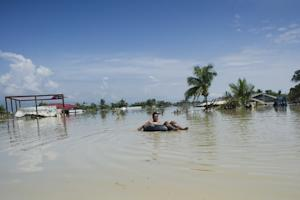 A flood-affected resident uses a make-shift raft to…