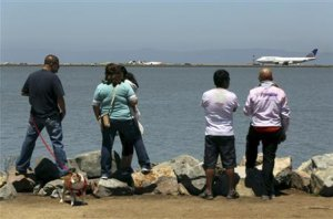 People look from a path along San Francisco Bay after an Asiana Airlines Boeing 777 that crashed while landing at San Francisco International Airport in San Francisco