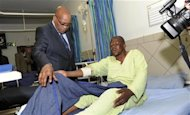 South Africa's President Jacob Zuma (L) chats with one of the injured miners during a courtesy visit in a hospital outside a South African mine in Rustenburg, 100 km (62 miles) northwest of Johannesburg, August 17, 2012. REUTERS/Kopano Tlape/Government Communications and Information Systems (GCIS)/Handout
