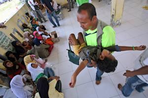 An aid worker carries a sick Rohingya boy at a temporary …